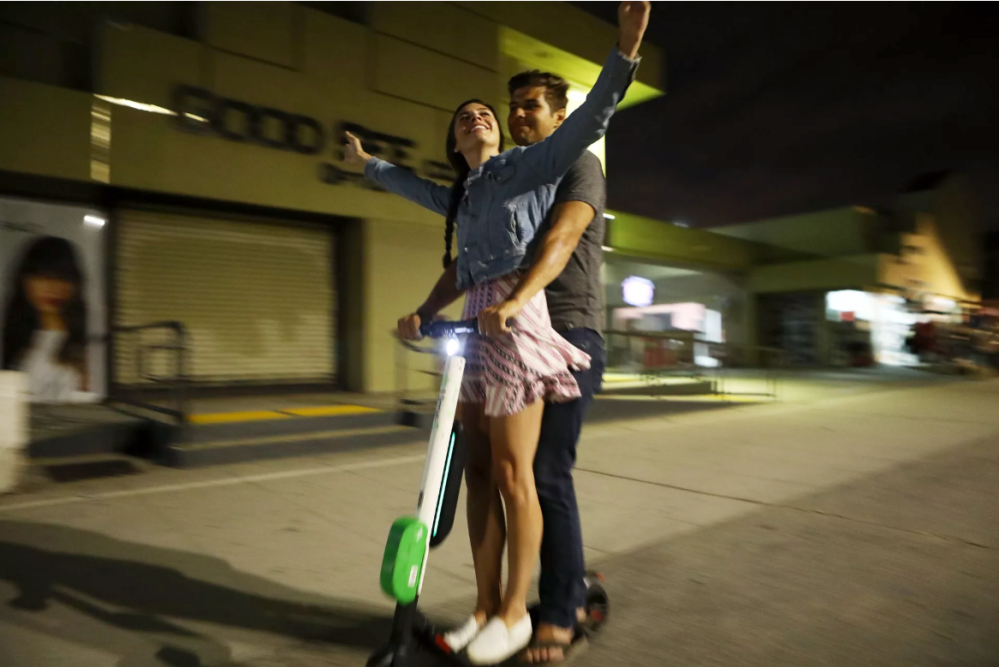 Tandem riding Lime scooter