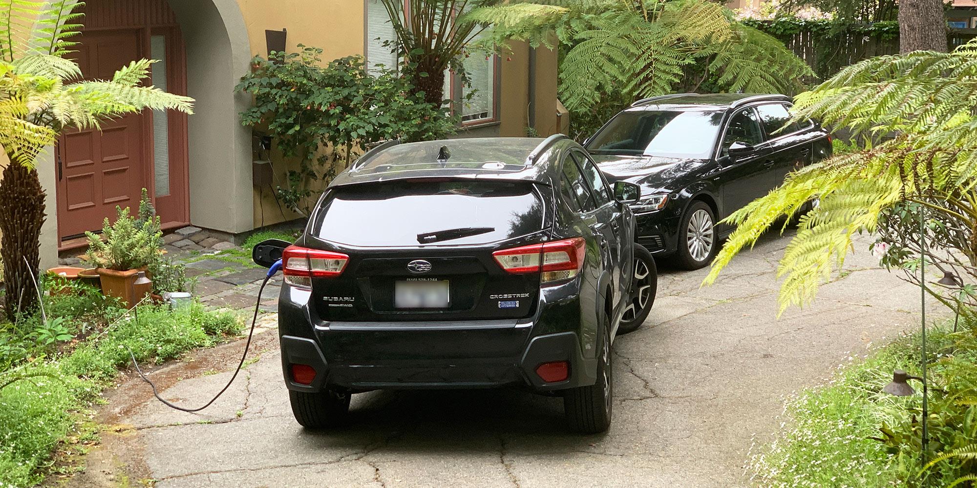 Subaru and Audi plug-in hybrids in a driveway